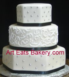 Three tier round and hexagon white fondant wedding cake with royal icing piping and silver dots