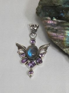 Contemporary organic Angel sterling pendant with oval Labradorite center stone and 7 faceted purple Amethyst gemstones, bezel-set in 925-hallmarked sterling silver, with intricately scrolled bail. Len