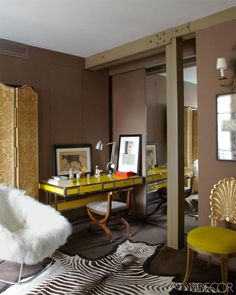 This bold sitting area combines color, texture and pattern in one cohesive, stylish space. The armchair by Carlo Colombo and a 1970s French desk are paired with a Biedermeier chair; the walls are painted in Farrow & Ball's Brinjal. See the rest of the home.   - ELLEDecor.com