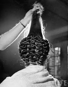 A man cold wrapping a woman's hair. (back) 1940 Photographer: David E. Scherman