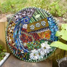 This 'Gaudi' inspired mosaic has been made with recycled stained glass set directly onto a new mirror which adds depth and brightness of colour to the stained glass.  There is a 1958 Half Crown coin nestled in the design.  Suitable for indoor or all year garden display. Fittings supplied.