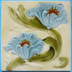 Antique majolica tile from the English maker Malkin Tile Co., c. 1885-1900, depicting swirling sky blue blooms on a cream field.