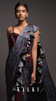 Plum ready pleated saree in crepe. It comes with a steel blue attached ruffle pallu in satin with floral print. Adorned with cut dana and beads work. Paired with a plum corset in velvet with sequins, cut dana and zardozi embroidered floral pattern. Designed with straps on the shoulders and corset neckline