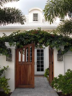 Quintessential beach house design and look with a walled front patio enclosure and peekaboo gates. Inviting yet private. Nice copper sconces for a welcoming warm light glow at night. A showy blue-white flowering potato vine (Solanum jasminoides) trellis over the gates would be a cool touch.