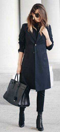 Nicoletta Reggio + height of chic sophistication + tailored trench coat + leather heels + simple cigarette pants + fashionable marriage + black and navy blue.  Jacket, Pants: Prada, Boots: Givenchy, Bag: Saint Laurent, Bracelet: Elements DonnaOro
