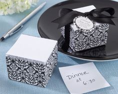 "A sweet, petite, handy sheet--our ""Damask Elegance"" Note Pad Wedding Favors are perfect for adding a touch of class and elegance to your special day. Purse-size and pretty in the vintage damask design, this chic note pad is sure to be the ""write"" favor for your next event!Size: Note pad measures 1 1/2"" h x 2"" w x 2"" d.Details: Stacked, white note pad paper with elegant black-and-white damask design on all four sides"