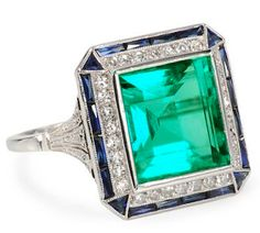 Art Deco Sublime: Emerald Diamond Sapphire Ring, Exceptional rectangular step cut natural Colombian emerald 6.3 carats, set in platinum, with thirty old single cut diamonds, synthetic sapphires and an additional sixteen sapphires line the edges. On the sides six more old single cuts add their spark bringing the estimated diamond total to .21 carats. Circa 1925.