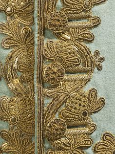 Detail of a gold embroidery on blue-grey woll with s-ing, bullion thread and handmade sequins. Beautiful buttons and buttonholes!