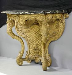 "CONSOLE ""AU MASCARON"", Régence , France ca. 1730. Wood richly carved with mask, cartouches, leaves, diamond patterns and ornamental frieze, and gilt. Grey/white marble top. Chips. 118x54x90 cm."