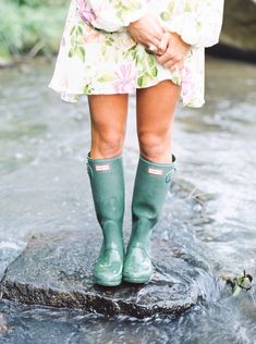 girl wearing green hunter boots and floral dress…