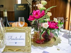 Mark and Rochelle, married January 2016 - Hot Pink and gold theme is right on trend - gold accented centrepieces and gorgeous pink vintage glass with hot pink flowers, gold frames display table names - Mission Estate Winery, Hawkes Bay.