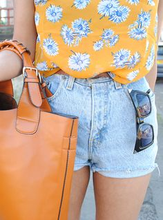 high waisted light blue demin shorts, bright orange/dark yellow top, black shades, and light brown bag