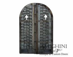 Rustic antique arched solid double doors make a charming garden entrance with their fantastic hand carved details. #antiquedoors #antiquegate #amighini