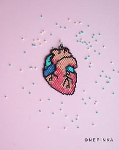 Neon heart - designed and hand beaded by NEPINKA Available as -a pendant with a gunmetal ball chain (70cm long (28)) -a necklace, you see on the second photo - with a black veins bow. For pendants I use finest Japanese glass beads - Miyuki Delica, each of identical shape and size. It ensures