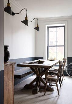 Chunky dark farm table in dining room with gray hardwood floor.