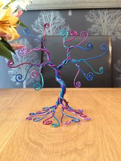 A handmade twisted wire tree for holding business cards, photos or name tags using green and white wire. It would be perfect to hold photographs.  It measures approximately 20cm (8 inches) tall by 20cm wide by 12cm (5 inches) by 12cm root base It has branches to hold 16 cards.They are for Sale on Etsy