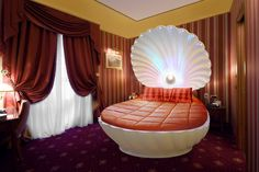 Pearly white clamshell bed with orange accents.