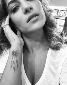 Creative propwork makes this tiny dreamcatcher tattoo appear as if it's