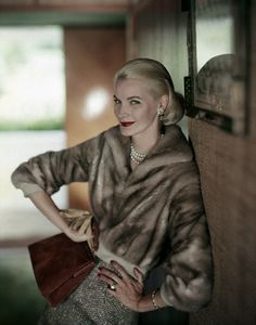 Harnett 1957 Sunny is wearing a short mink jacket with a tweed skirt and holding…