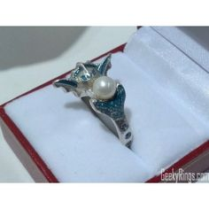 The ring is made out sterling silver to closely resemble Vaporeon blowing a ball of steam. The steam is represented with a pearl. There are natural topazes set around the band, while the blue color is achieved with jewelry enamel.  Other metal options, enamel colors and gemstones are available. Want to customize it? Contact us.