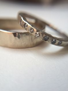 14 karat White Gold Hammer Textured Wedding Band Set  These Wedding Rings are such fun to create! I love hammering gold, and texturing metal!  The texture is hammered in very subtle and rustic. And with a texture like this you don't have to worry about being hard on jewelry the more worn they get just adds to the character!  His solid hammered band and hers a nice squared hammered band with gypsy set tiny salt and pepper diamonds. Conflict free. The ladies band pairs very nicely with…