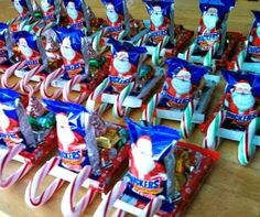It's also a great idea to bring to your kids classroom for a holiday party. Please note to check ahead of time for peanut allergies!! You can find individual snicker candies with Santa's face on the front (which works perfectly that he's driving the sleigh!)  Start by gluing two candy canes facing upwards onto a kit-kat bar. This is going to be the base of the sleigh. Add some hersheys chocolates and top with a kiss on top. This makes it look like Santa's bag of presents!