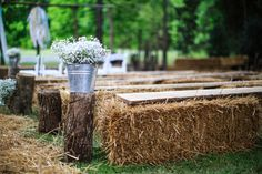 Hay bales and boards as seating for backyard wedding ceremony.