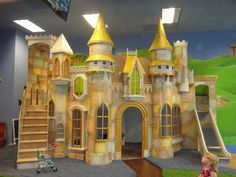 This big indoor playhouse, the Wizard of Oz Castle, is meant for spaces with lots of kids playing at once. Includes slide, staircase, and hand painting. #kidsindoorplayhouse
