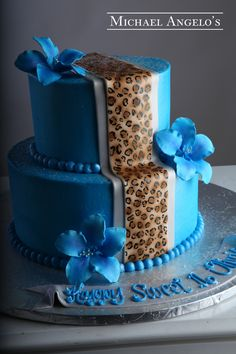 Floral Cheetah #48Milestones  This is a two-tier round iced in blue buttercream. A double fondant overlay is included in light blue and cheetah print. Gum paste flowers accent each layer for the perfect finish.