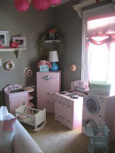 Pretend play area. Pottery Barn Kids pink retro kitchen set.  I found the bronze bundt pans at the salvation army for a buck a piece.