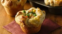 """2 c frozen mixed vegetables 1 c diced cooked chicken 1 can condensed cream of chicken soup 1 can Grands Flaky Layers biscuits Heat 375° In md bowl combine vegetables chicken & soup mix well Press each biscuit into 5 1/2"""" round Place 1 round in each of 8 greased regular-size muffin cups.  Firmly press in bottom and up side forming 3/4"""" rim Spoon 1/3 c chicken mix into each Pull edges dough over filling pleat & pinch dough gently to hold in place Bake 375° 20-22"""" til golden brown. Cool 1"""""""