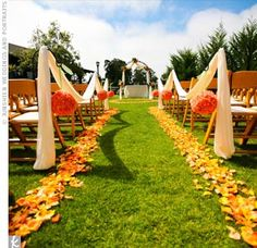 Bright, colorful outdoor wedding aisle with yellow petals, orange pomanders and white draping.