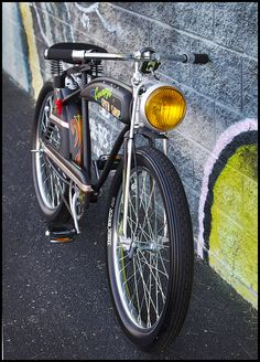 An old vintage yellow Chevy fog light modified with a cheap LED flashlight mounted to a custom bike.