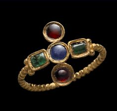 Gold ring, the ribbed hoop terminating in beaded shoulders supporting the cruciform bezel set with two emeralds in oblong settings, centred on a third emerald in a round setting flanked above and below by two rubies similarly set Late Roman, 4th century A.D., hoop perhaps later.