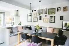 Built in banquette seating with scattered cushions and framed pictures on the walls in dining room of Victorian house renovation by Imperfect Interiors, Beth Dadswell, London, Photography by Leanne Dixon | Remodelista