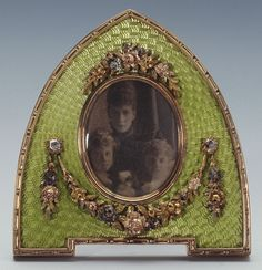 Fabergé red gold photograph frame in the form of a Gothic arch, with guilloché green enamel and mounted with three-colour gold swags and garlands set with rose diamonds.Workmaster Victor Aarne. Photograph of Princess Alexandra with Lady Alexandra and Lady Maud Duff.