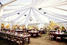 This is a nice alternative to the typical reception tent. I really like the chandeliers hanging above to contrast the primitive tables and chairs.
