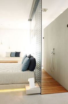 Interesting way to incorporate an open shower concept in a hotel room.  The wood floor really warms up the space. #bathroom #hotel