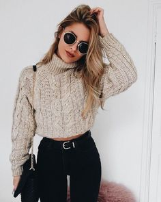 Beige cable knit sweater with black jeans.