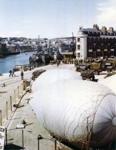 """""""American troops load onto LSIs at a port in Britain where barrage balloons have been anchored for protection against strafing and low level bombings."""" (US National Archives 111-C-1169)"""