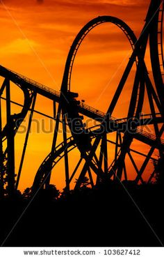 stock photo : silhouette of a roller coaster at a purple sunset with people on the ride