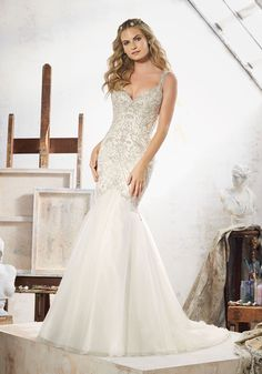 Morilee by Madeline Gardner 'Maeve' 8107 | Glamorous Fit & Flare Wedding Dress Featuring Crystal Beaded Embroidery on Tulle. The Dramatic Open Back is Accented with Covered Button Detail. Colors Available: White/Silver, Ivory/Silver, Light Gold/Silver. Shown in Light Gold/Silver.