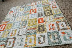 Orange, turquoise, grey, and mustard quilt
