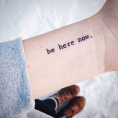 Wrist tattoo saying 'Be here now' on Ashley.