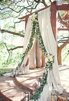 Brides.com: . A wooden ceremony altar covered with draped fabric, a greenery garland and pale-hued flowers, created by The Nouveau Romantics.