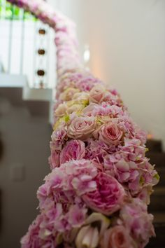 Flower covered banister, leading down to the reception (ALL carnations??)