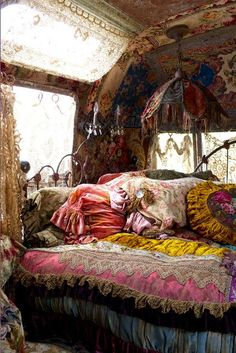 This is Bohemian gypsy to the extreme. The ornate linens, lace, fringe, wrought iron bed and vintage wallpaper all combine together to create this ultra feminine look.