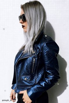 A textured faux leather moto jacket featuring an asymmetrical zipper front, a notched collar, front zipper pockets, shoulder lapels, and long sleeves.