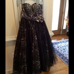 PRICE DROP !!  PROM GOWN Beautiful prom gown.  Worn only once.whole gown is made of 100%polyester.The design is an animal print, black,grey,white. The whole top is sewn with black,white and grey sequins. Has a large bow at waist-line with rhinestones designs. The bottom has three layers of material. One layer blk.poly ,two layers of blk. tulle netting, top layer is blk. netting over a layer of the animal print material.  It ties up the back.Gorgeous! Gorgeous!   Make me an offer !  Let's…