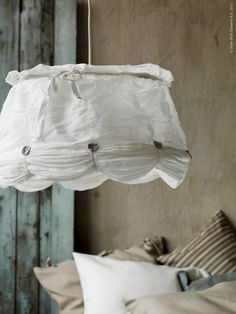 Ikea lampshade... totally diy-able with scrap fabric and some buttons... Looks like a circle skirt on a frame
